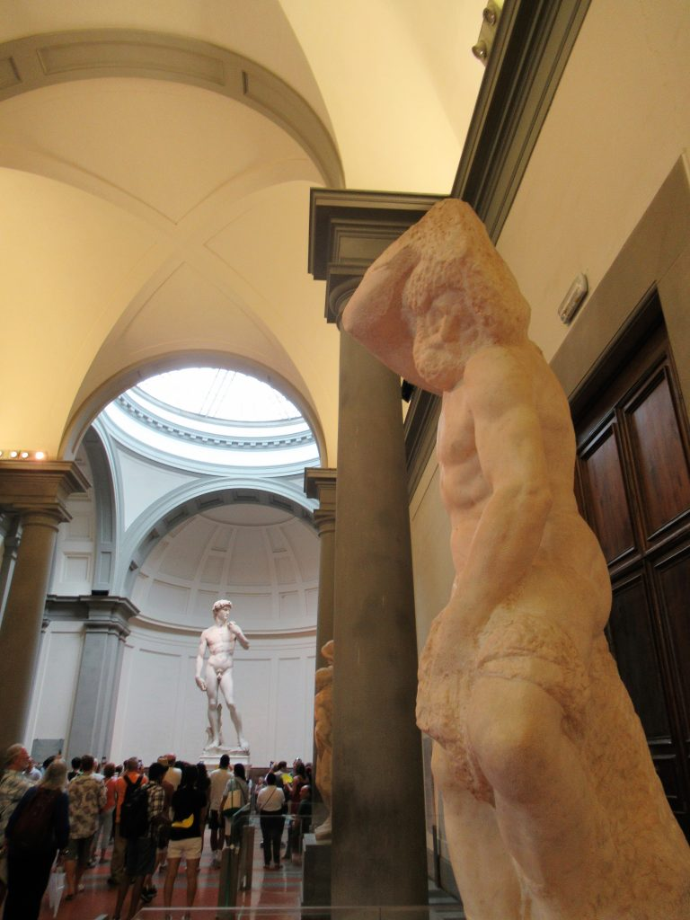 Michelangelo's Statue of David is at the end of a long hallway, lined by several of Michelangelo's unfinished sculptures, at the end of the The Accademia Gallery in Florence, Italy